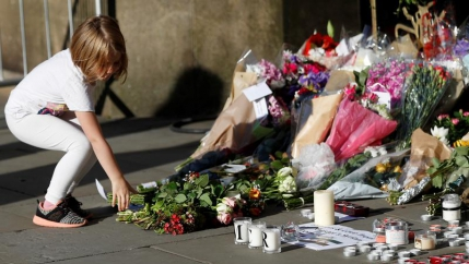 A girl leaves flowers for the victims of an attack on concert goers at Manchester Arena.